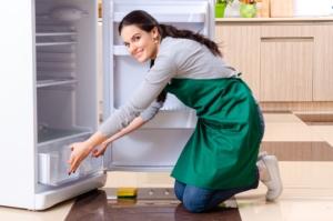 women defrosting fridge